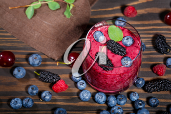 Glass of smoothies and a bunch of fresh berries on a dark wooden background