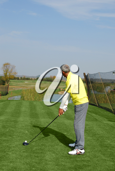 Male golf player preparing for hit
