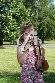 happy little girl with violin in park