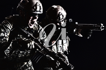 Half length low angle studio shot of pair two special forces soldiers in field uniforms with weapons attacking shouting, portrait on black background