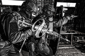 Police special forces, counter-terrorism tactical team fighters, private security company guards aiming guns while moving forward under cover of ballistic shield on anti narcotics raid, desaturated