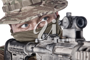 Close-up studio portrait of army elite forces soldier, commando fighter, special operations squad shooter in camo bonnie, face paint camouflage, aiming service rifle, observing area with optical sight
