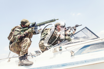 Anti terrorist squad fighters, SEALs team soldiers armed service rifle with optical sigh and silencer, rushing on speed boat, screaming commands to comrades, chasing and attacking enemy on water