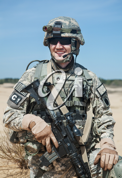Portrait of United states airborne infantry man with arms, camo uniforms dress. Combat helmet on, tactical light, radio microphone on his mouth