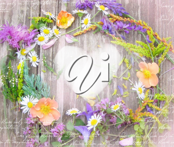 Beautiful wreath of wildflowers from Carpathian Valleys on vintage wooden table. Composition of wild flowers in country chic style on shabby background with heart and place for your text or picture.