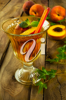 Refreshing drink, iced green tea with peaches and mint in a glass on a dark wooden background, close up, vertical, selective focus