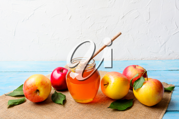 Glass honey jar with dipper and apples, copy space. Rosh hashanah concept. Jewesh new year symbols.