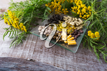 Ayurvedic herbal pills on the glass plate and tansy yellow flowering plant. Healthy life concept