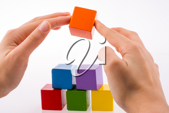 Hand playing with colorful cubes on a white background