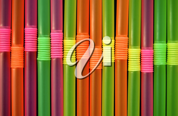 Drinking straws against a black background. Abstract pattern.