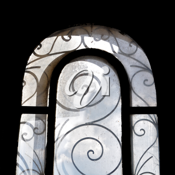 Sunlight on dusty arched window with vintage decorative metalwork motif.
