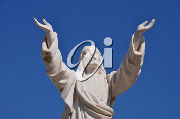Jesus Christ with hands raised in blessing under blue sky. Marble funerary statue.