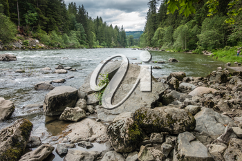 A view of the Snoqualmie River with rocks in the foreground.
