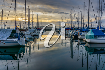 The sun sets behind moored boats  at the Des Moines Marina in Des Moines, Washington.