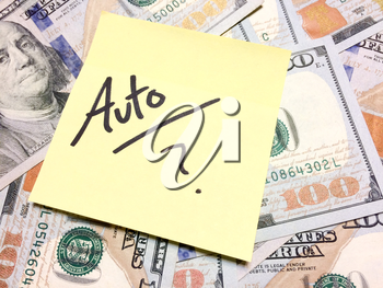 American cash money and yellow sticky note with text Auto with question mark in black color aerial view