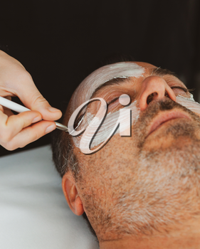 Middle-aged man in a beauty salon with a facial mask.