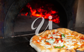 Cooking a margherita pizza in a wood oven.