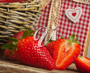 Beautiful strawberries with cookbook on wooden table