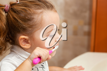 Portrait of cute little girl with blonde hair which cleaning tooth with brush and toothpaste in bathroom.
