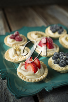 Strawberry, blueberry and pistachios tartlets on green tray on a wooden table