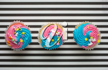 Three cupcakes with blue and pink icing on a black and white lined background