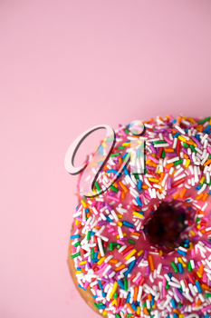 Close up of a donut with pink icing and candies on a pink pastel background
